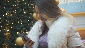 Ένα νέο κορίτσι γράφει ένα μήνυμα στο τηλέφωνο closeup απόθεμα βίντεο