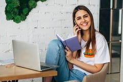 Ένα νέο κορίτσι είναι ένα freelancer που λειτουργεί στον καφέ με ένα lap-top και που χαμογελά στη κάμερα Στοκ φωτογραφία με δικαίωμα ελεύθερης χρήσης