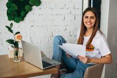 Ένα νέο κορίτσι είναι ένα freelancer που λειτουργεί στον καφέ με ένα lap-top και που χαμογελά στη κάμερα Στοκ Εικόνα
