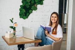 Ένα νέο κορίτσι είναι ένα freelancer που λειτουργεί στον καφέ με ένα lap-top και που χαμογελά στη κάμερα Στοκ εικόνες με δικαίωμα ελεύθερης χρήσης