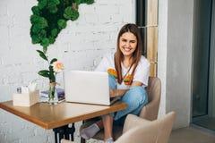 Ένα νέο κορίτσι είναι ένα freelancer που λειτουργεί στον καφέ με ένα lap-top και που χαμογελά στη κάμερα Στοκ Εικόνες