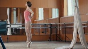 Ένα νέο κορίτσι εκτελεί χαριτωμένα τα τεχνάσματα acrobatics στο στούντιο Στοκ Φωτογραφία