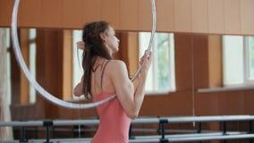 Ένα νέο κορίτσι εκτελεί χαριτωμένα το acrobatics με τη γυμναστική στεφάνη Στοκ εικόνες με δικαίωμα ελεύθερης χρήσης
