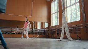 Ένα νέο κορίτσι εκτελεί χαριτωμένα το acrobatics με τη γυμναστική στεφάνη Στοκ φωτογραφία με δικαίωμα ελεύθερης χρήσης