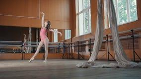 Ένα νέο κορίτσι εκτελεί χαριτωμένα τα τεχνάσματα acrobatics στο στούντιο Στοκ φωτογραφία με δικαίωμα ελεύθερης χρήσης