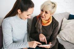 Ένα νέο κορίτσι εξηγεί σε μια ηλικιωμένη γυναίκα πώς να χρησιμοποιήσει μια ταμπλέτα ή παρουσιάζει κάποια εφαρμογή ή σας διδάσκει  στοκ φωτογραφία με δικαίωμα ελεύθερης χρήσης