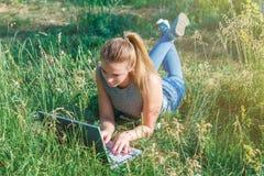 Ένα νέο κορίτσι επικοινωνεί με την αγαπημένη μέσω ενός υπολογιστή υπαίθρια που βρίσκεται στην πράσινη χλόη στοκ φωτογραφία με δικαίωμα ελεύθερης χρήσης