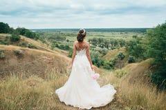 Ένα νέο κορίτσι, η νύφη σε ένα μακρύ γαμήλιο φόρεμα, την γυρίζουν πίσω και κοιτάζει επίμονα στην απόσταση στον ποταμό και ένα όμο Στοκ Εικόνες