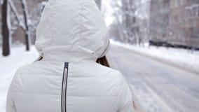 Ένα νέο κορίτσι θέτει για τη κάμερα μια κρύα χειμερινή ημέρα Κρύο χιονιού φιλμ μικρού μήκους
