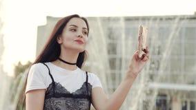 Ένα νέο κορίτσι ισιώνει την τρίχα της εξετάζοντας τη κάμερα ενός smartphone απόθεμα βίντεο