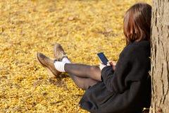 Ένα νέο κορίτσι κάθεται από ένα δέντρο, σε ένα πάρκο φθινοπώρου με ένα τηλέφωνο Στοκ Εικόνες