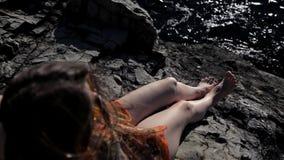 Ένα νέο κορίτσι κάθεται σε έναν βράχο και εξετάζει τη θάλασσα απόθεμα βίντεο