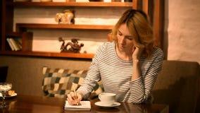 Ένα νέο κορίτσι κάθεται σε έναν πίνακα σε έναν καφέ σκεπτόμενος, στενό σημειωματάριο με το μολύβι απόθεμα βίντεο