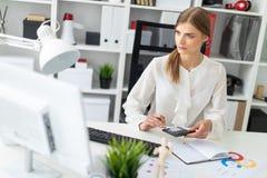 Ένα νέο κορίτσι κάθεται σε έναν πίνακα στο γραφείο, κρατά ένα μολύβι στο χέρι της και βασίζεται σε έναν υπολογιστή στοκ εικόνες