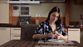Ένα νέο κορίτσι κάθεται στην κουζίνα στο σπίτι της και τρώει φιλμ μικρού μήκους