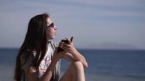 Ένα νέο κορίτσι κάθεται στην παραλία στα γυαλιά ηλίου και κάνει ένα τηλεφώνημα απόθεμα βίντεο