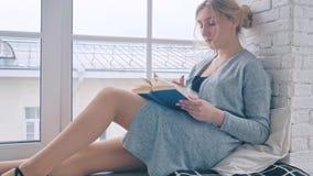 Ένα νέο κορίτσι κάθεται στο windowsill και διαβάζει ένα βιβλίο απόθεμα βίντεο