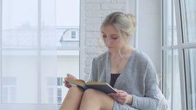 Ένα νέο κορίτσι κάθεται στο windowsill και διαβάζει ένα βιβλίο φιλμ μικρού μήκους