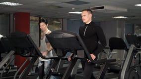 Ένα νέο κορίτσι και ένας τύπος που κάνουν τις ασκήσεις στη γυμναστική treadmill Αθλητισμός, μετακίνηση, υγεία φιλμ μικρού μήκους
