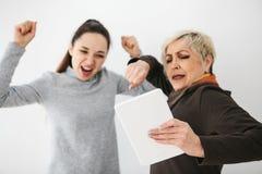 Ένα νέο κορίτσι και μια ηλικιωμένη γυναίκα εξετάζουν κάτι που ενδιαφέρει στην ταμπλέτα και παρουσιάζουν συγκινήσεις Επικοινωνία,  στοκ φωτογραφίες