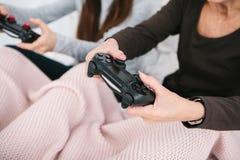 Ένα νέο κορίτσι και μια ηλικιωμένη γυναίκα παίζουν μαζί σε ένα τηλεοπτικό παιχνίδι Κοινό χόμπι Οικογενειακή ζωή Επικοινωνία στοκ εικόνες με δικαίωμα ελεύθερης χρήσης