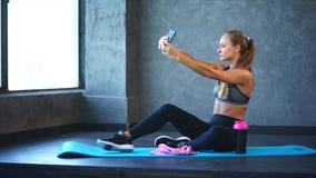 Ένα νέο κορίτσι με έναν καλό αριθμό κάνει selfie σε ένα κινητό τηλέφωνο στη γυμναστική απόθεμα βίντεο