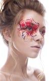 Ένα νέο κορίτσι με ένα δημιουργικό makeup υπό μορφή λουλουδιού κόκκινος-χρυσού στο μάτι της Όμορφο πρότυπο στην εικόνα ενός λουλο στοκ εικόνες