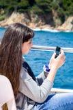 Ένα νέο κορίτσι με μακρυμάλλη εξετάζει το τηλέφωνο καθμένος σε ένα σκάφος αναψυχής στοκ εικόνες με δικαίωμα ελεύθερης χρήσης