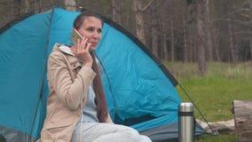 Ένα νέο κορίτσι με μακρυμάλλη κάθεται κοντά σε μια μπλε σκηνή στα ξύλα και μιλά στο τηλέφωνο απόθεμα βίντεο