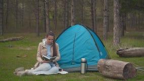 Ένα νέο κορίτσι με μακρυμάλλη κάθεται κοντά σε μια μπλε σκηνή στο δάσος και διαβάζει ένα βιβλίο απόθεμα βίντεο