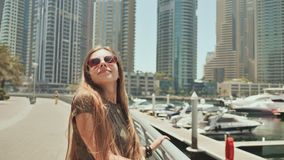 Ένα νέο κορίτσι με μακρυμάλλη και μια καλή διάθεση περπατά κατά μήκος του αναχώματος της μαρίνας του Ντουμπάι απόθεμα βίντεο