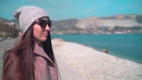 Ένα νέο κορίτσι με μακρυμάλλη στα γυαλιά, ένα καπέλο και ένα παλτό στο  απόθεμα βίντεο