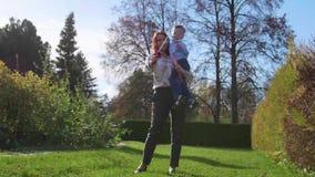 Ένα νέο κορίτσι με ένα παιδί που παίζει στο πάρκο στο χορτοτάπητα Το κορίτσι κάνει τις φυσαλίδες σαπουνιών, και το παιδί τις πιάν απόθεμα βίντεο
