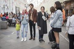 Ένα νέο κορίτσι με τα αυτιά anime και μια γυναίκα στην ηλικία στέκονται σε μια για τους πεζούς οδό στην αναμονή Στοκ Εικόνες