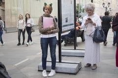 Ένα νέο κορίτσι με τα αυτιά anime και μια γυναίκα στην ηλικία στέκονται σε μια για τους πεζούς οδό στην αναμονή Στοκ φωτογραφία με δικαίωμα ελεύθερης χρήσης