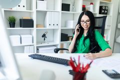 Ένα νέο κορίτσι με τα γυαλιά στο γραφείο μιλά στο τηλέφωνο και κρατά ένα μολύβι στο χέρι της Στοκ φωτογραφίες με δικαίωμα ελεύθερης χρήσης