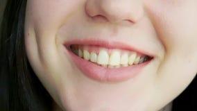 Ένα νέο κορίτσι με τα μεγάλα χείλια γελά και χαμογελά φιλμ μικρού μήκους
