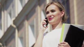 Ένα νέο κορίτσι με τα ξανθά μαλλιά στέκεται κοντά στο κτίριο γραφείων και μιλά στο τηλέφωνο Υπάρχουν έγγραφα στα χέρια μου απόθεμα βίντεο