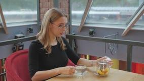 Ένα νέο κορίτσι με τα ποτήρια που κάθεται σε έναν καφέ χύνει το τσάι από teapot σε ένα φλυτζάνι γυαλιού απόθεμα βίντεο