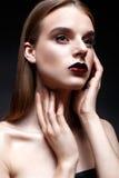 Ένα νέο κορίτσι με τη μακριά ευθεία τρίχα και το φωτεινό βράδυ makeup Όμορφο πρότυπο με τα κόκκινα χείλια Στοκ φωτογραφία με δικαίωμα ελεύθερης χρήσης