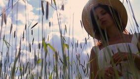 Ένα νέο κορίτσι με τη μακριά σκοτεινή τρίχα που στέκεται σε έναν πράσινο τομέα απόθεμα βίντεο