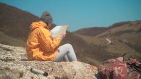 Ένα νέο κορίτσι με τη μακριά σκοτεινή τρίχα σε ένα κίτρινο σακάκι και μια γκρίζα ΚΑΠ κάθεται στα βουνά και εξετάζει έναν χάρτη το απόθεμα βίντεο