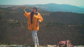 Ένα νέο κορίτσι με τη μακριά σκοτεινή τρίχα σε ένα κίτρινο σακάκι και μια γκρίζα ΚΑΠ στέκεται σε ένα βουνό και παίρνει ένα selfie απόθεμα βίντεο