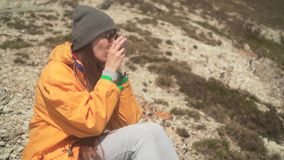 Ένα νέο κορίτσι με τη μακριά σκοτεινή τρίχα σε ένα κίτρινο σακάκι, μια γκρίζα ΚΑΠ και τα γυαλιά κάθεται στο βουνό και πίνει το τσ απόθεμα βίντεο