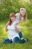 Ένα νέο κορίτσι με τη μητέρα σε μια πράσινη χλόη Στοκ φωτογραφία με δικαίωμα ελεύθερης χρήσης