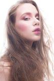 Ένα νέο κορίτσι με το χαλαρό μακρυμάλλες και φωτεινό δημιουργικό makeup Το όμορφο πρότυπο με τα κόκκινα χείλια και κοκκινίζει σε  Στοκ Εικόνες