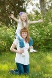 Ένα νέο κορίτσι με το mather σε μια πράσινη χλόη Στοκ Εικόνες