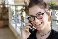 Ένα νέο κορίτσι με orthodontics τα στηρίγματα που φορούν eyeglasses είναι συζήτηση στοκ φωτογραφία