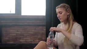 Ένα νέο κορίτσι πίνει το νερό από ένα πλαστικό μπουκάλι σε ένα στούντιο απόθεμα βίντεο