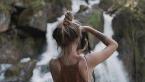 Ένα νέο κορίτσι παπαράτσι παίρνει τις εικόνες ενός όμορφου μεγάλου καταρράκτη που στέκεται στις πέτρες στη ζούγκλα E απόθεμα βίντεο